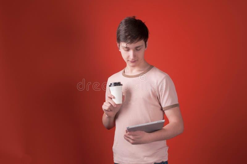Nastolatek w beżowej t koszulowej pozycji z kawą w papierowej filiżance i patrzeć cyfrową pastylkę zdjęcia royalty free