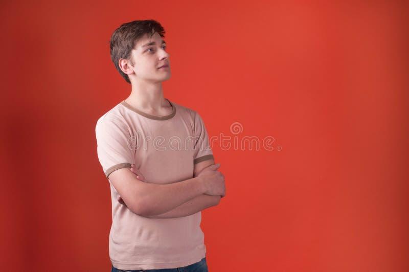 Nastolatek w beżowej t koszulowej pozycji z krzyżować rękami i patrzeć daleko od na pomarańczowym tle fotografia royalty free