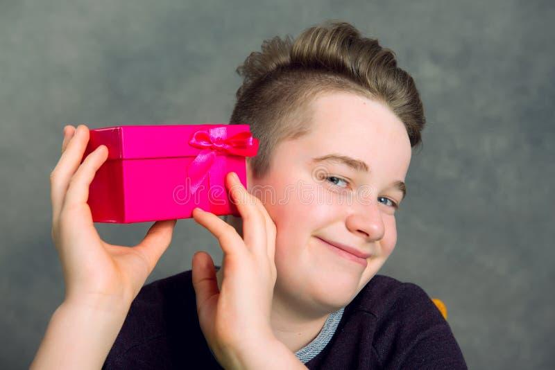 Nastolatek w brown bluzie sportowa z czerwonym prezenta pudełkiem zdjęcie royalty free