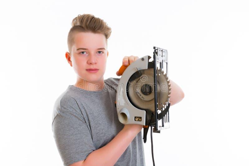 Nastolatek w fachowym szkoleniu używa kółkową rękę zobaczył obraz stock