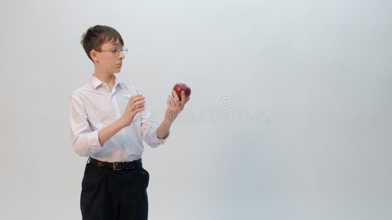 Nastolatek w szkłach w zdziwień spojrzeniach przy czerwonym jabłkiem Śmieszna emocja w wizerunku znakomity uczeń Uczniowski facet obrazy royalty free