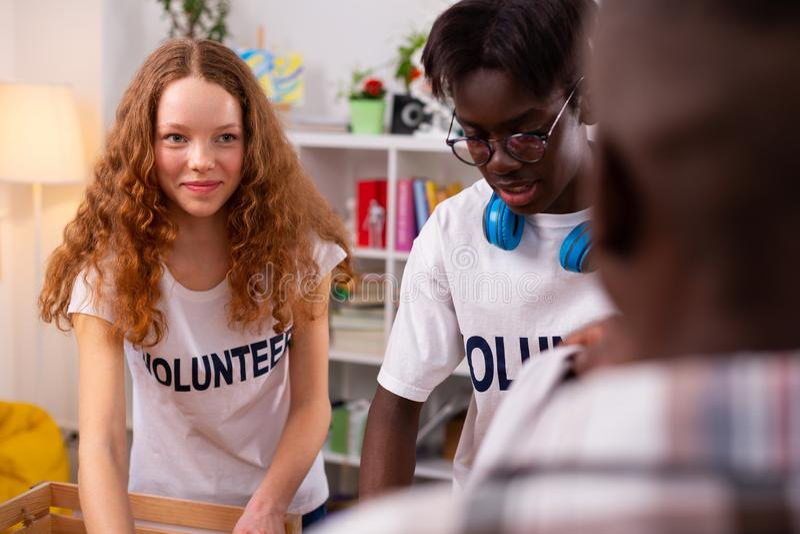 Nastolatek w szkieł zbierać odziewa dla darowizny z przyjaciółmi obraz stock