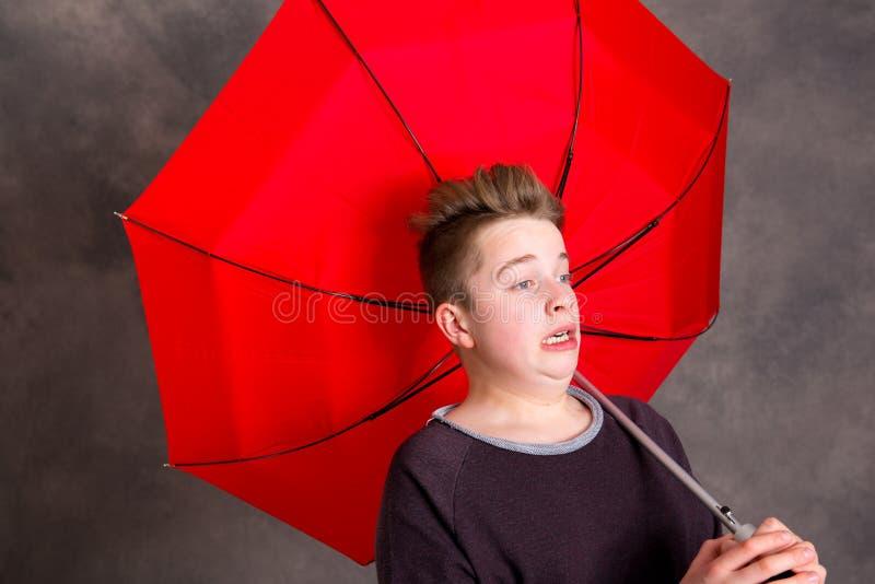 Nastolatek z czerwoną parasolową pozycją w silnym popióle obraz stock