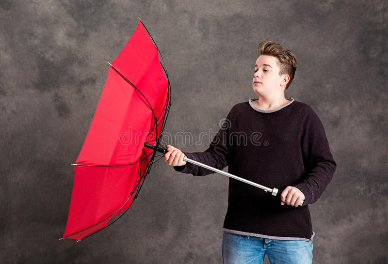 Nastolatek z czerwoną parasolową pozycją w silnym popióle obraz royalty free