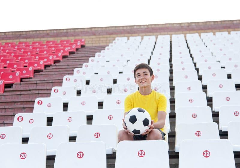 Nastolatek z piłki nożnej piłką w jego wręcza obsiadanie na trybunach zdjęcia royalty free