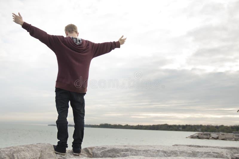 Nastolatek z rękami w powietrzu zdjęcie royalty free