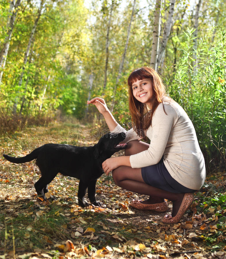 Nastolatka dziewczyna i czarny labradora aporteru szczeniak zdjęcie royalty free