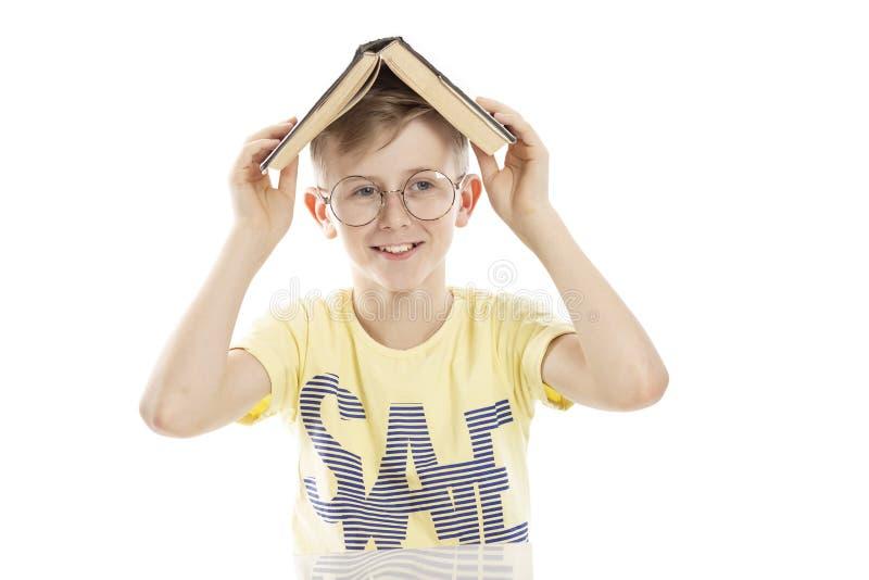 Nastolatka facet w szkłach z książką na jego głowie jest roześmiany Siedzi sto?em Nad bia?ym t?em zdjęcie royalty free