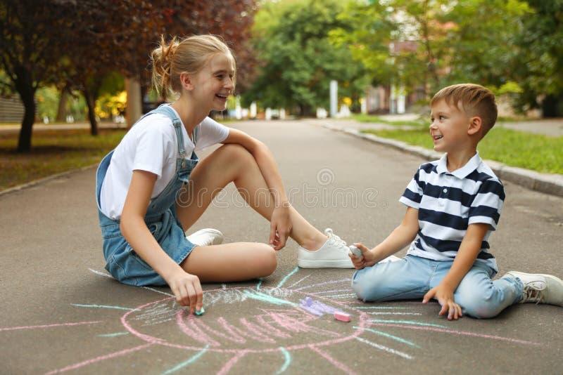 Nastolatka i śliczny chłopczyk, który świeci słońcem kredami fotografia royalty free