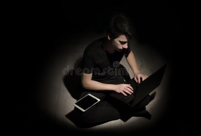Nastolatka młody człowiek pracuje na laptopie i pastylce na czarnym backgro obraz stock