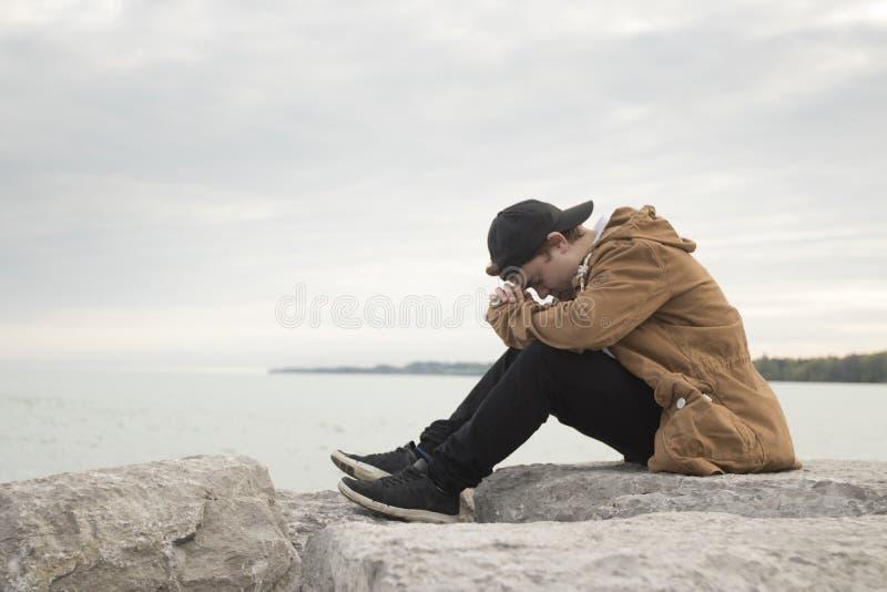 Nastolatka obsiadanie na skałach i modleniu fotografia stock