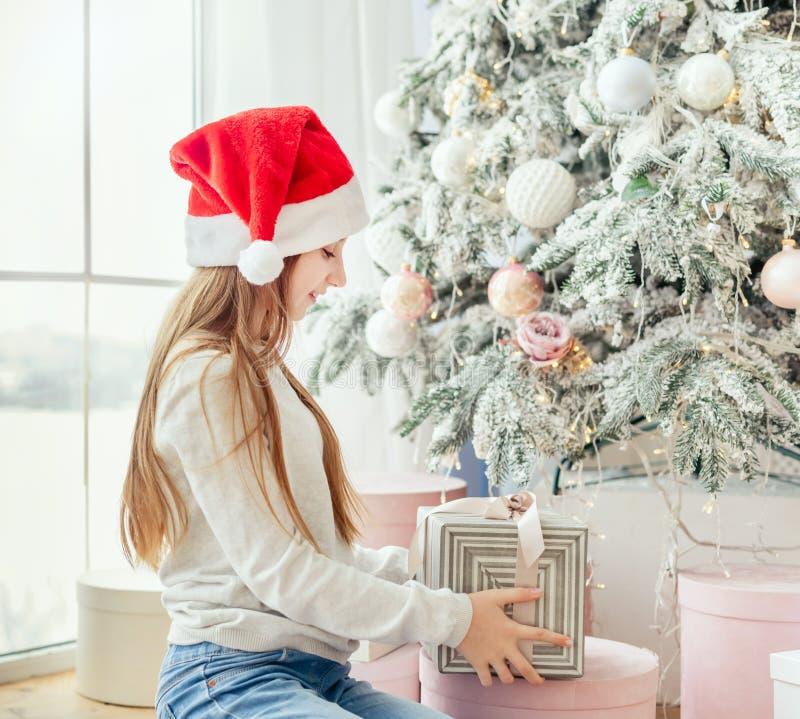 Nastolatka otwiera prezent w pobliżu choinki świątecznej fotografia royalty free