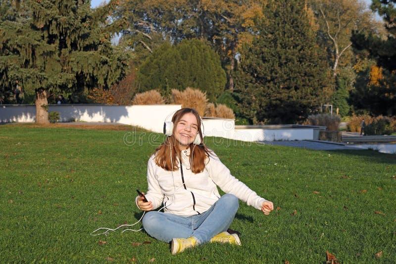Nastolatka słucha muzyki ze swojego smartfona i śpiewa w parku fotografia stock
