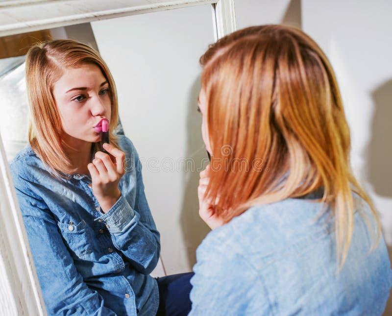 Nastolatka stosować uzupełniał w jej twarz, stawia na różowy lipstic fotografia royalty free