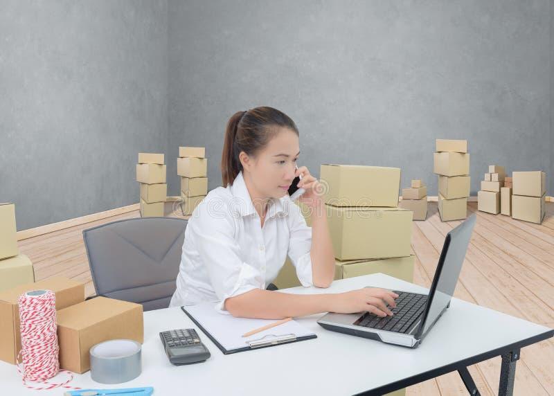 nastolatka właściciela biznesowej kobiety praca przy biurem z smartphone, laptop dla online zakupy pisze rozkazie zdjęcia royalty free