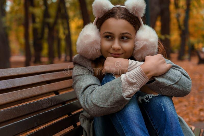 Nastolatka w futrzanych słuchawkach siedzi na ławce jesienią obraz stock