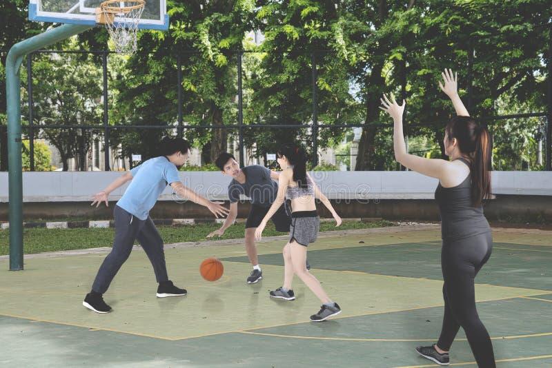 Nastolatkowie bawić się koszykówkę wpólnie przy outdoors fotografia stock