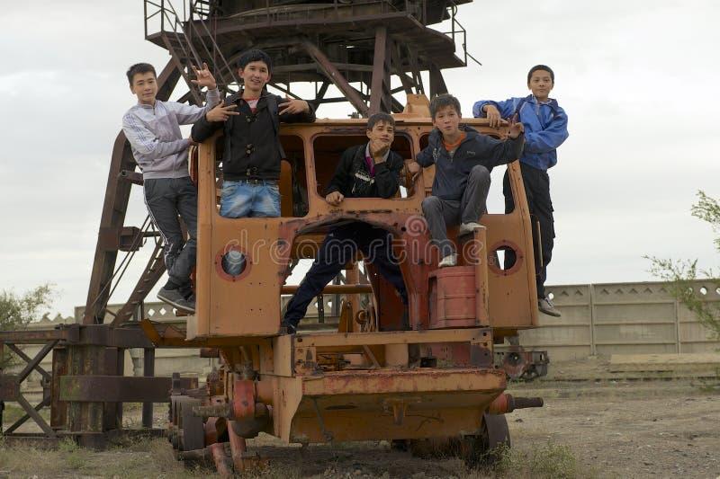 Nastolatkowie bawić się przy zaniechanym portu morskiego wyposażeniem w Aralsk, Kazachstan obrazy stock
