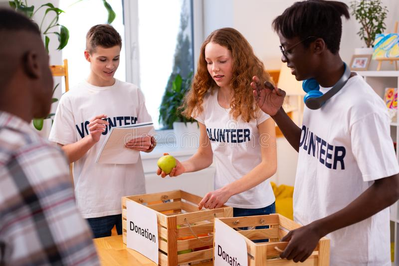 Nastolatkowie stawia jedzenie dla darowizny w pudełka wpólnie fotografia royalty free