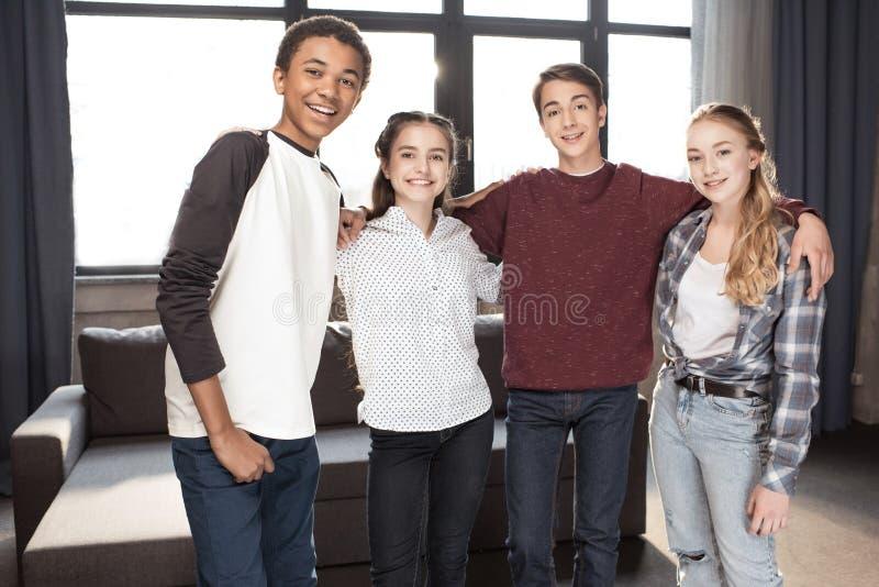 Nastolatkowie stoi wpólnie i ono uśmiecha się przy kamerą indoors, nastolatkowie ma zabawy pojęcie zdjęcie royalty free