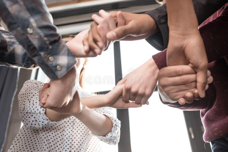 Nastolatkowie trzyma ręki wpólnie indoors, nastolatkowie ma zabawy pojęcie zdjęcia stock