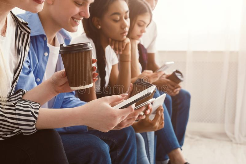 Nastolatkowie u?ywa telefony, gaw?dzi w og?lnospo?ecznych sieciach obraz royalty free