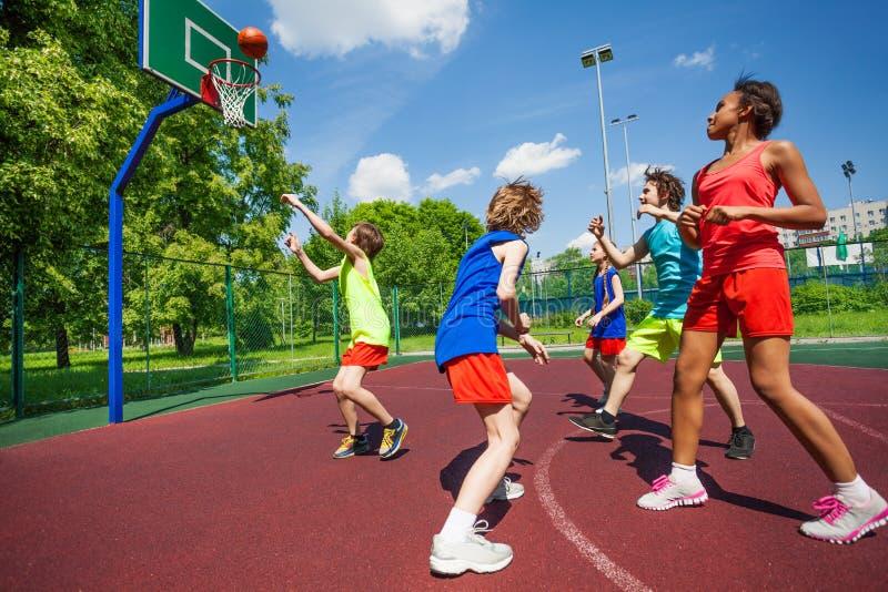 Nastolatkowie w kolorowych mundurach bawić się koszykówkę obrazy stock