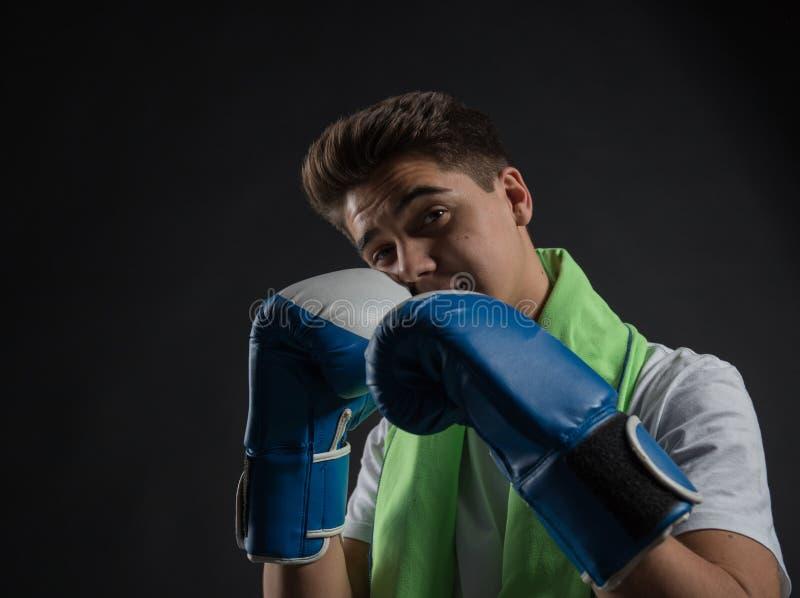 Nastoletni bokser pozuje z błękitnymi i białymi bokserskimi rękawiczkami w fotograficznym studiu zdjęcia stock