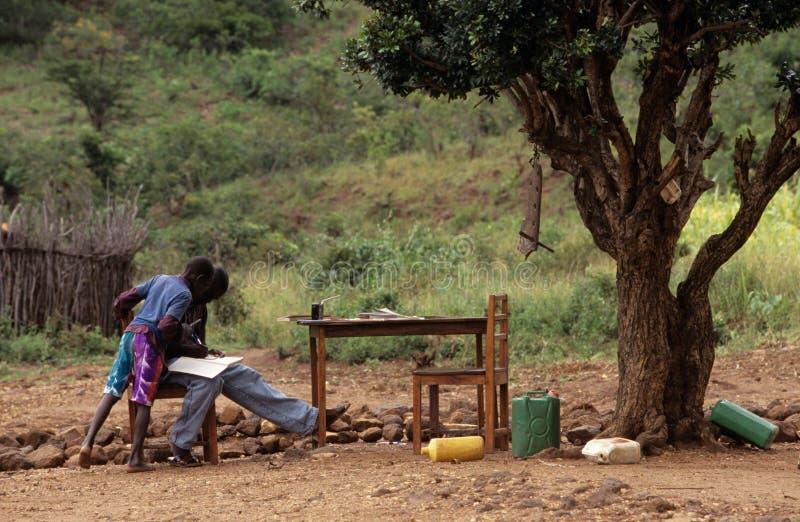 Nastoletni chłopacy studiuje outdoors, Mozambik zdjęcie stock