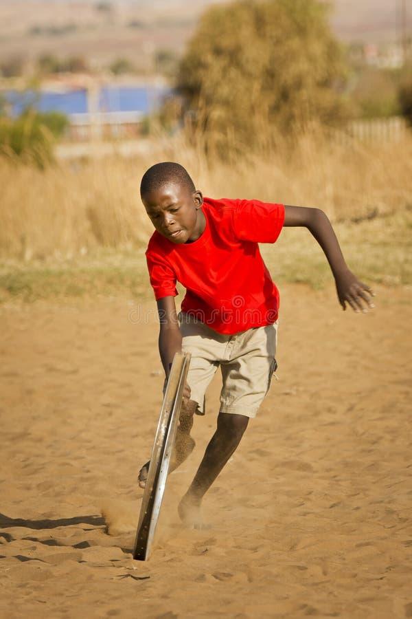 Nastoletni Chłopak Bawić się z Kołem - Więcej Akcja zdjęcie stock