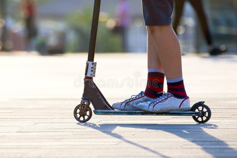 Nastoletni chłopak jazda w mieście na hulajnodze Sporty i hobby obraz royalty free