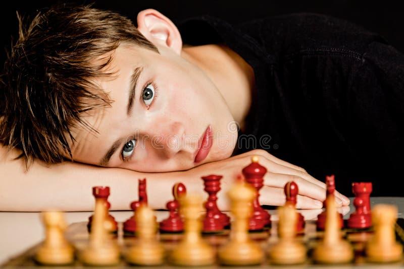 Nastoletni Chłopak Odpoczynkowa głowa na Stołowej Pobliskiej Szachowej desce obrazy stock