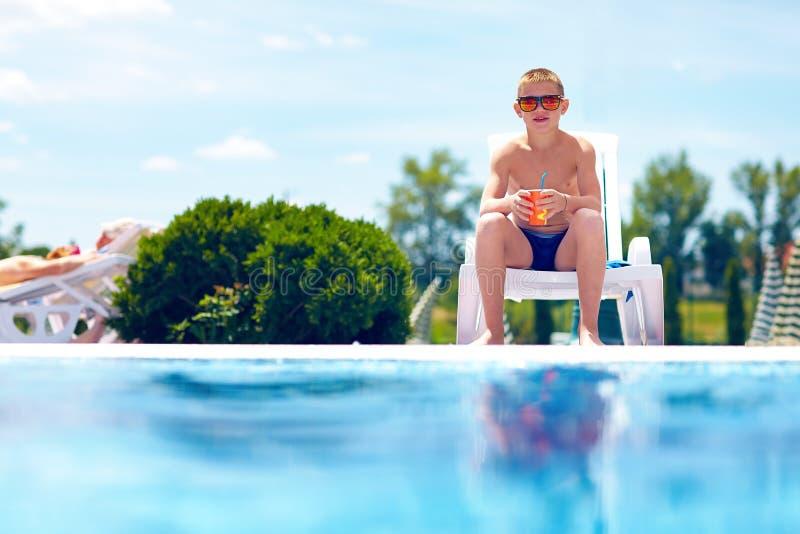 Nastoletni chłopak relaksuje blisko basenu obraz stock