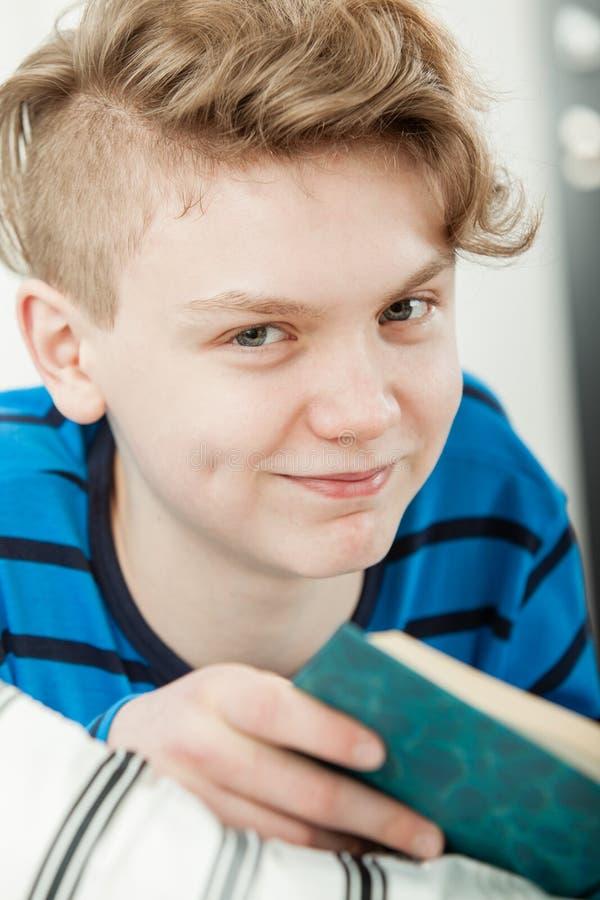 Nastoletni Chłopak Relaksuje w łóżku Podczas gdy Czytelnicza książka zdjęcie royalty free