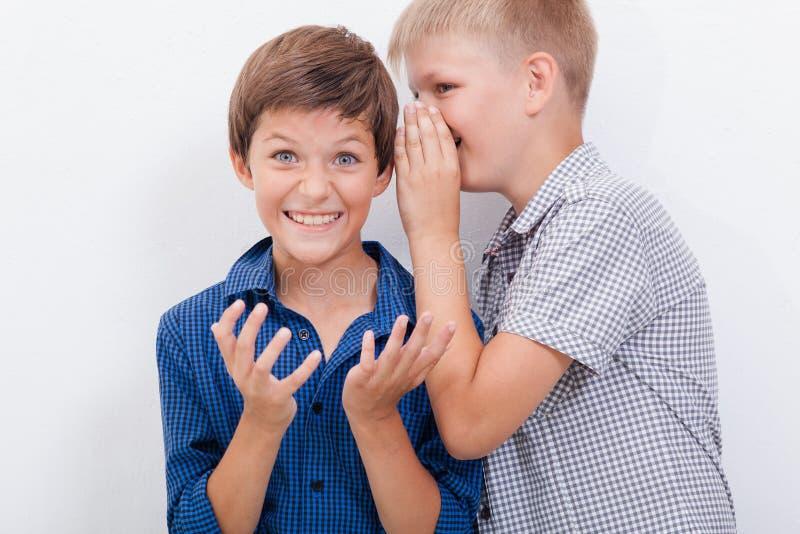 Nastoletni chłopak szepcze w ucho sekret zdjęcia royalty free