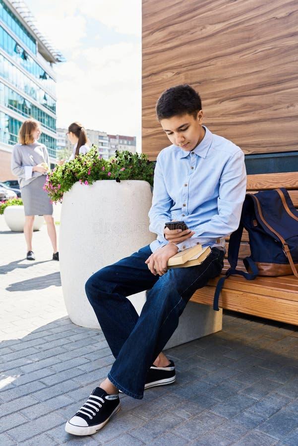 Nastoletni Chłopak Używa Smartphone w Szkolnym jardzie zdjęcia royalty free