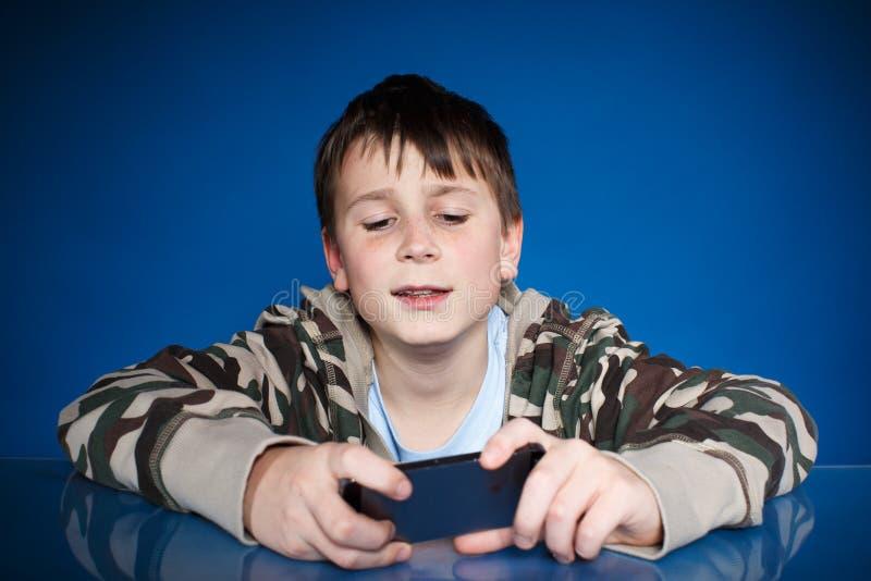 Nastoletni chłopak z telefonem w ręce zdjęcia royalty free