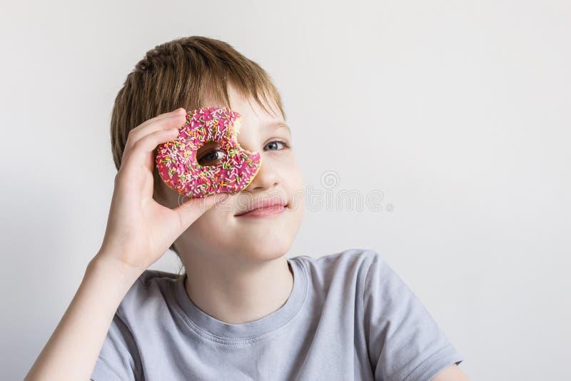 Nastoletni chłopiec spojrzenia w dziurę gryźć pączek i śmieszni grymasy obrazy royalty free