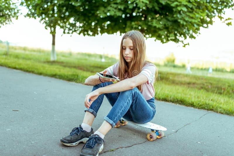 Nastoletni dziewczyny 11-14 lat, siedzi w rękach łyżwa W lata mieście w przypadkowych cajgach i różowej koszulce Komunikacja wewn zdjęcia royalty free