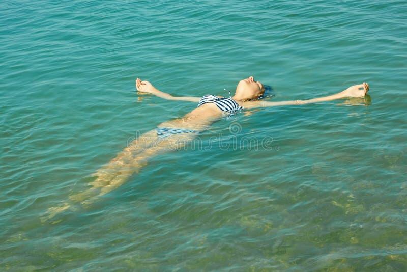 Nastoletni dziewczyny lying on the beach na wody morskiej powierzchni obrazy royalty free
