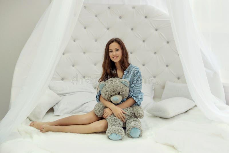 nastoletni dziewczyny obsiadanie na białym round łóżku w sypialni i uściśnięć misiu obraz royalty free