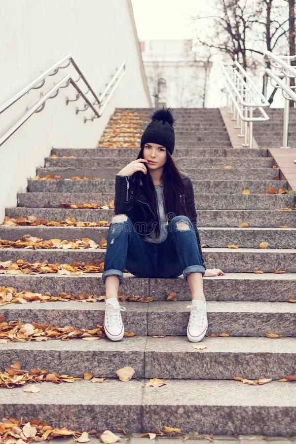 Nastoletni dziewczyny obsiadanie na schodkach przeciw grunge ścianie zdjęcie stock