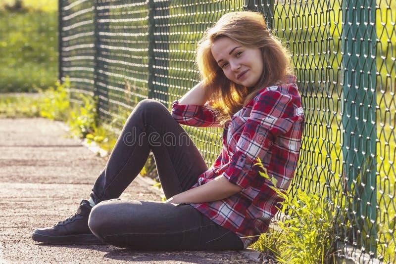 Nastoletni dziewczyny obsiadanie na szkolnym boisku obrazy stock