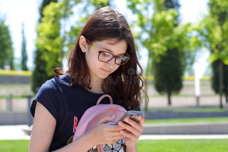 nastoletni dziewczyny telefon kom?rkowy Portret młoda dziewczyna w górę tła zieleni drzewa dalej obraz royalty free
