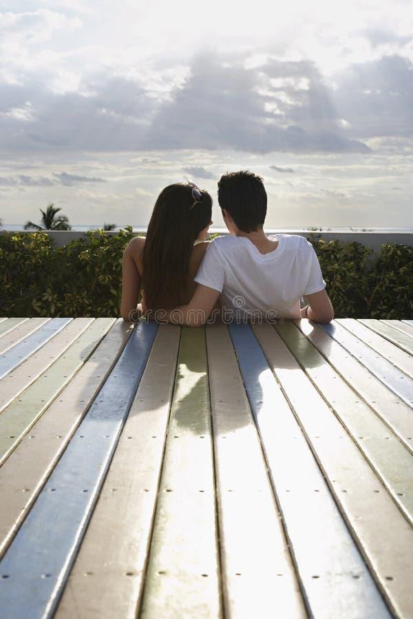 Nastoletni pary obsiadanie Na pokładzie Patrzeje widok obrazy royalty free