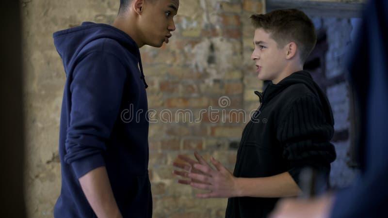 Nastoletni poniżający głupek, biedny nastolatek znęcać się bogatej chłopiec, dorastająca agresja zdjęcie stock