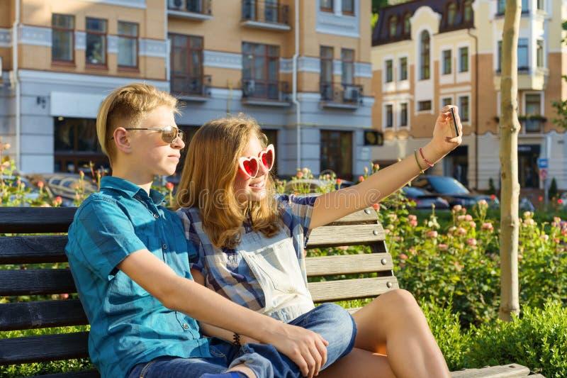 Nastoletni przyjaciele dziewczyna i chłopiec obsiadanie na ławce w mieście, opowiadający, patrzejący w telefonie, robi selfi obraz stock