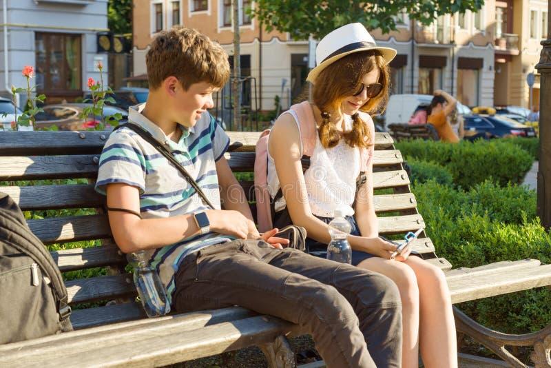 Nastoletni przyjaciele dziewczyna i chłopiec obsiadanie na ławce w mieście patrzeje w telefonie, ono uśmiecha się, opowiadający,  zdjęcie stock