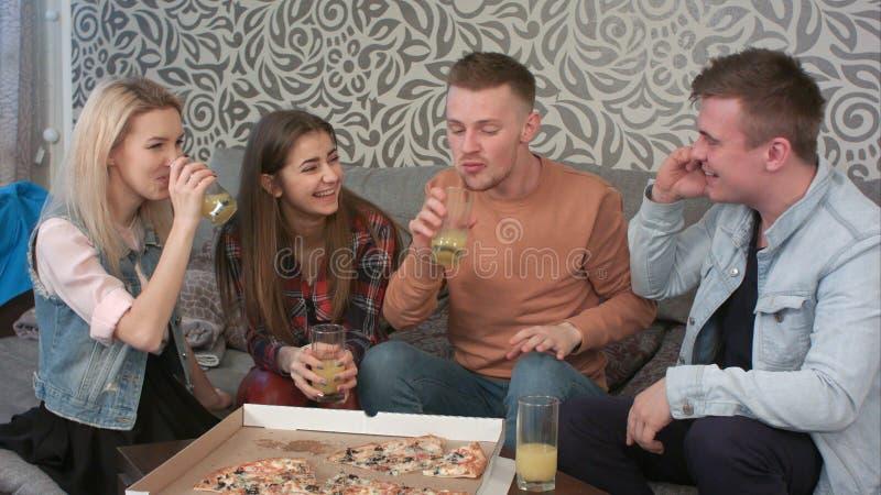 Nastoletni przyjaciele siedzi na kanapie i dzwoni someone, są naprawdę szczęśliwi słuchać obrazy royalty free