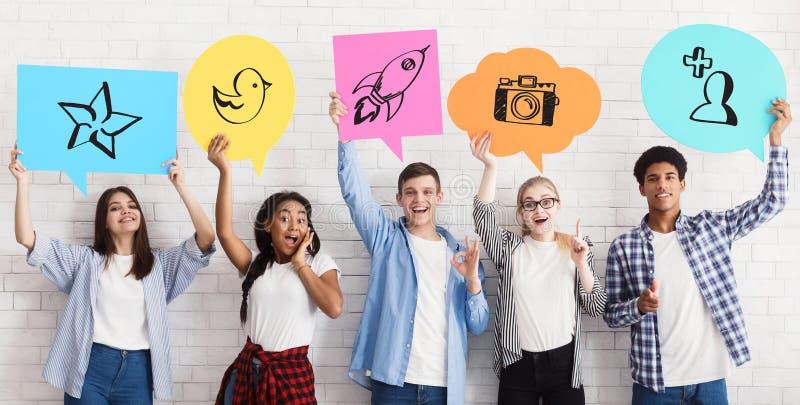 Nastoletni przyjaciele Trzyma Og?lnospo?eczne Medialne ikony, biel ?ciana fotografia royalty free